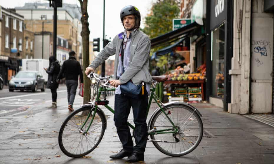 Jeremy Deller wearing his bike helment and holding his bike in a north London street
