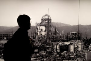 A visitor walks past a mural of the Atomic Bomb Dome