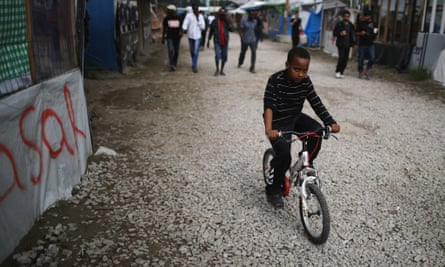 A boy rides his bicycle in the Calais migrant camp.
