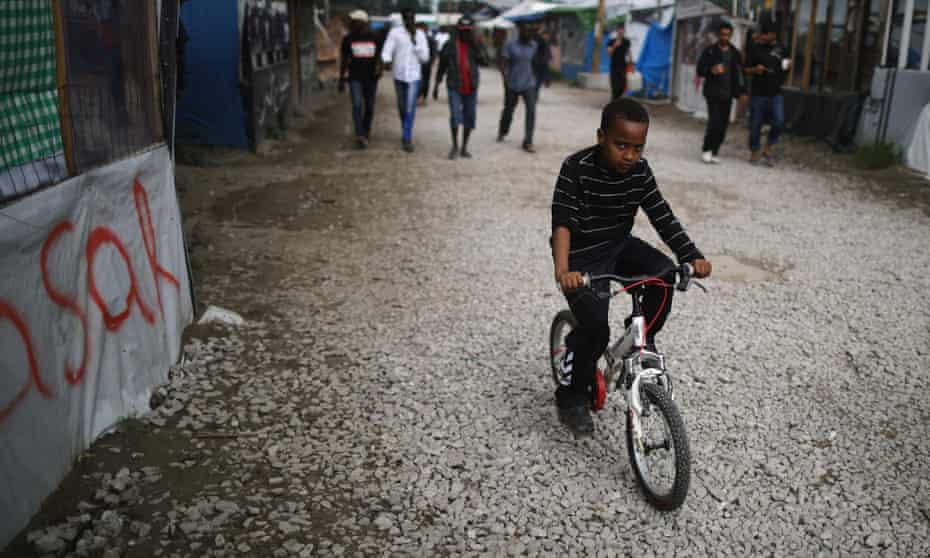 A young boy rides his bicycle in the Calais migrant camp.