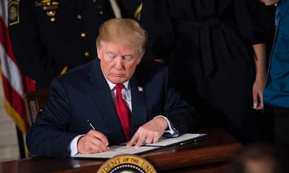 Donald Trump signs a presidential memorandum declaring the opioid crisis a public health emergency, in the East Room at the White House in Washington on 26 October 2017.