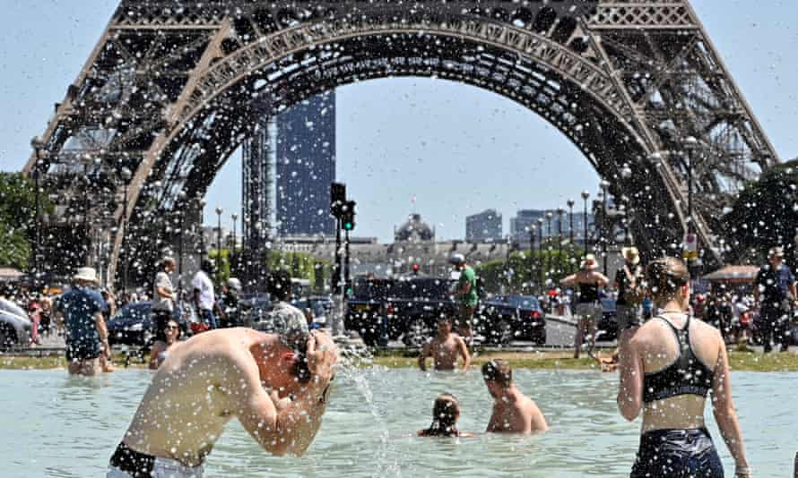 People cool off in the Trocadéro fountains, near the Eiffel Tower, during a heatwave in France on 29 June 2019.