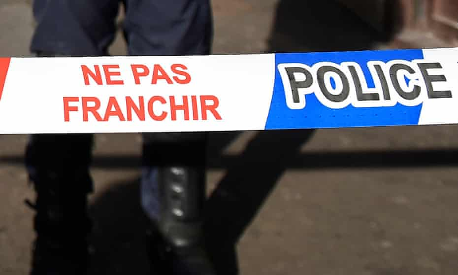 French police stand behind a police cordon.