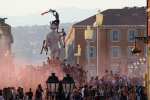 People wave flags and climb statues in central Nice