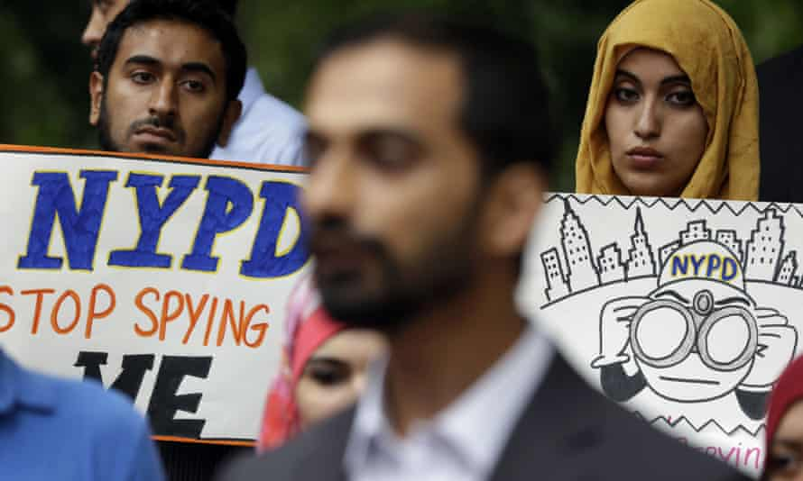 People hold signs at a 2013 rally to protest New York police department surveillance tactics.