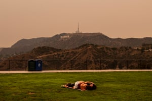 A couple kisses under an orange overcast sky in the afternoon in Los Angeles, California on 10 September 2020