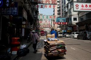 Man carries bundle of cardboard in Hong Kong.