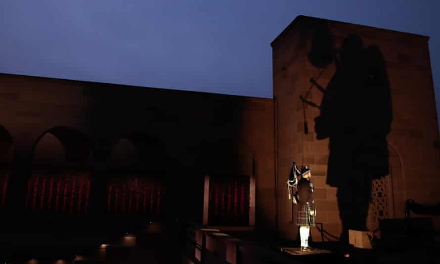 The shadow of a man playing bagpipes on the wall of the Australian War Memorial in the dawn light
