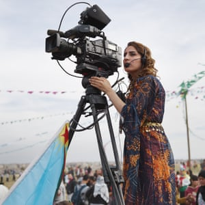 A camera operator streaming footage to a local Kurdish channel films an International Women's Day celebration.
