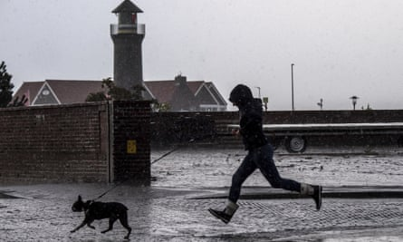 A woman runs with her dog past the Memmertfeuer lighthouse in Juist, Germany