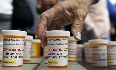People who have lost loved ones to OxyContin and opioid overdoses leave protest messages written on pill bottles outside the headquarters of Purdue Pharma in Stamford, Connecticut on 17 August 2018.