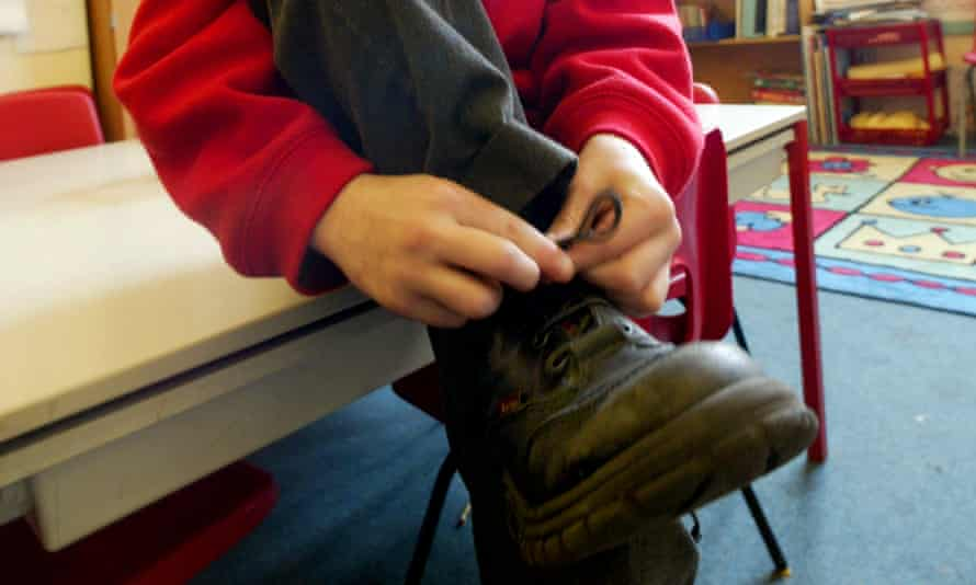 A child does up his shoelaces