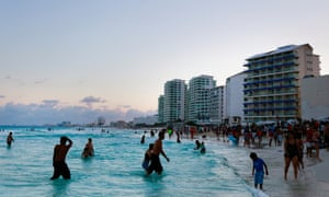 <br>Visitors wade at the shore of the beach in Cancun, Mexico in April 2015.