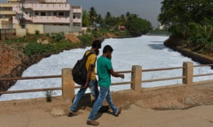 Pedestrians cover their noses as they cross a bridge over a frothing canal, which once carried water from Bellandur Lake to Varthur Lake, in east Bangalore in 2015.