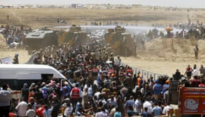 Turkish military use water cannon to stop Syrian refugees as they wait behind border fences
