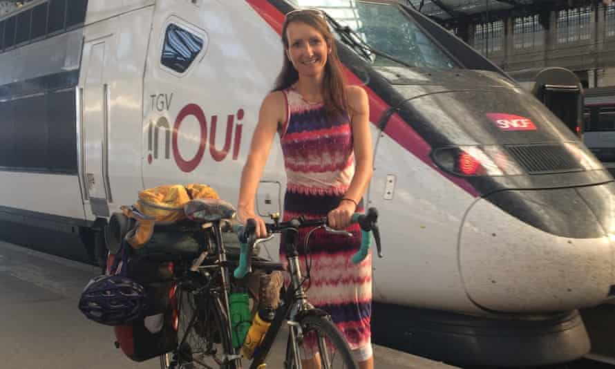 Anna Hughes with her heavily laden bike at the station, the front of a train behind