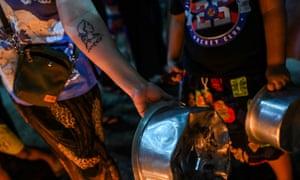 Μια γυναίκα δείχνει ένα τατουάζ της Aung San Suu Kyi καθώς χτυπάει γλάστρες και τηγάνια μπροστά στο στρατιωτικό πραξικόπημα