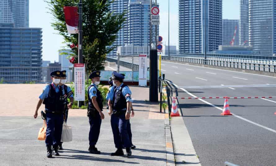 Petugas polisi berkumpul di desa Olimpiade, di mana kasus positif Covid pertama dikonfirmasi.