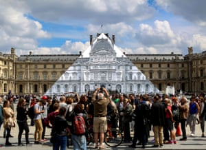 French artist and photographer JR's installation at the Louvre pyramid, which he covered with an anamorphic picture