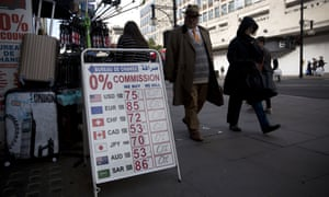 People walk past a bureau de change currency rate sign on Oxford Street in London