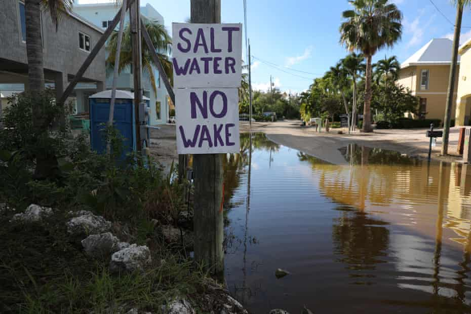 A sign reads 'Salt Water No Wake' as ocean water floods a street in Key Largo in October 2019.