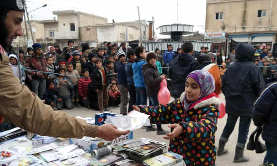 Photo purportedly shows Islamic State militant (left) distributing soft drinks, sweets and biscuits along with religious pamphlets to a young girl in Raqqa in January.