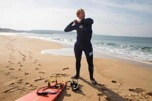 Cotton puts on his protective under-armour and wetsuit as he prepares for a paddle-surf in relatively tranquil conditions at Nazaré.