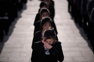 A woman wipes away tears as she waits to pay her respects