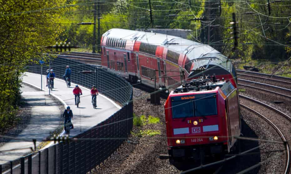 Commuters cycle beside a train on the new bicycle highway, RS1, that is set to span more than 60 miles in western Germany.
