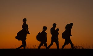 Refugees walk along a railway line after crossing the border from Serbia into Hungary in August 2015.
