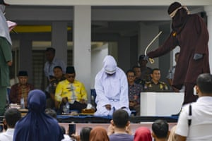 Banda Aceh, Indonesia: A woman is whipped in public by a member of the Sharia police