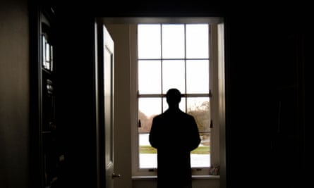 Man in overcoat standing looking out of window