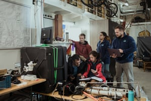 UNCW scientists gather round a screen showing real-time data from sensors.