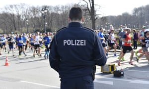 A German police officer stands guard as runners participate in the Berlin half-marathon.