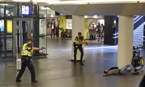 Dutch police officers point their guns at a wounded man who was shot by police at the central railway station in Amsterdam.