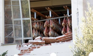 Legs of prosciutto hang inside an earthquake-hit building in Norcia, Italy.