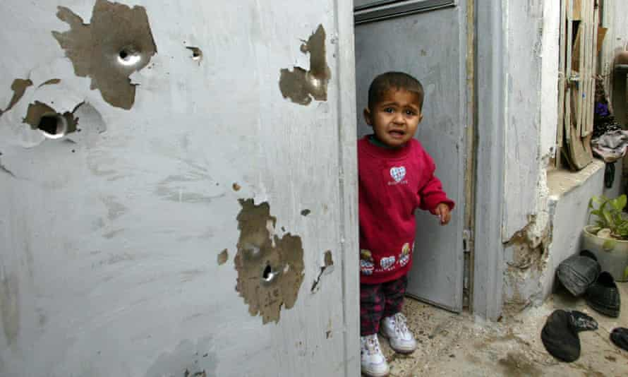 Child in bullet-riddled doorway