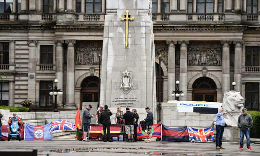 Former military personnel stand in front of the cenotaph in George Square, Glasgow, on Saturday.
