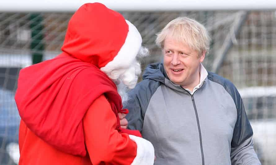Boris Johnson with a man dressed as Santa Claus while out campaigning in Stockport, Greater Manchester, this weekend.