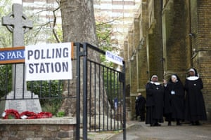 Nuns walk outside a polling station in London.