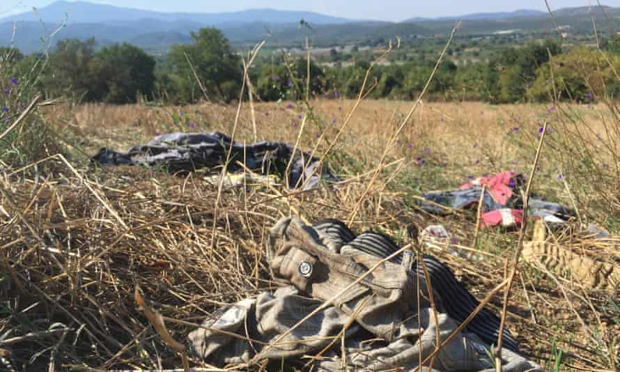 Clothes discarded by asylum seekers, a few metres from of Macedonia, which can be seen beyond the line of trees.