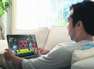 man watching football on laptop