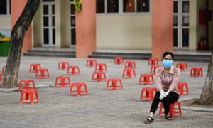 A woman waits at a makeshift rapid testing centre as Vietnam records a rise in coronavirus in Hanoi on 31 July 2020.