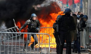 Police deal with a fire on the Champs Élysées during Bastille Day military parade in Paris.