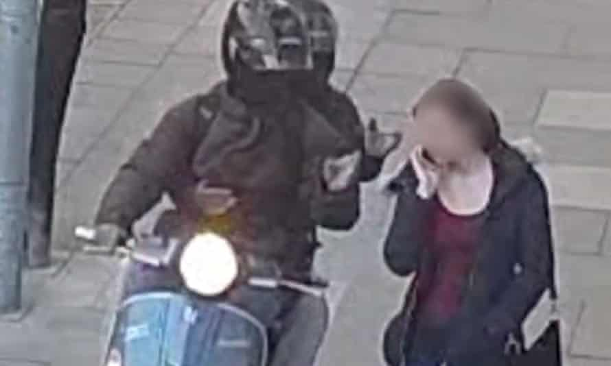 Still from a video issued by the Metropolitan police of riders on a moped trying to steal a mobile phone from a woman in London.