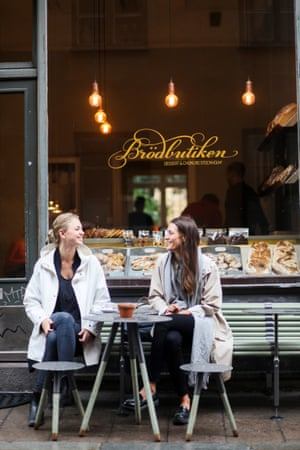 Two young women sitting at a table outside a Swedish cafe