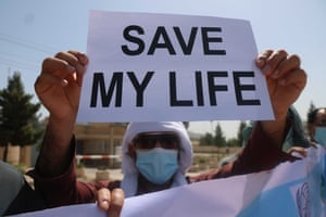 A man holds a sign with the words 'save my life' at a protest outside the Independent Human Rights Commission, in Herat, Afghanistan