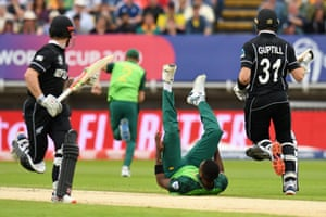 South Africa's Lungi Ngidi dives but fails to stop the ball as New Zealand's Martin Guptill (right) and his captain Kane Williamson add runs.