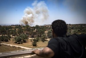 Smoke rises from nearby buildings in Espiaa, watched by a GNA fighter