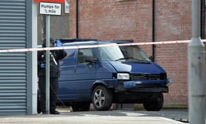 A bomb disposal officer inspects the van driven by Adrian Ismay following the car bomb attack in Belfast